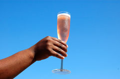 Hand with glass of wine. Hand of black woman with champagne glass of sparking rose wine; blue sky background Stock Images