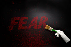 Hand in glove with the brush painting the text fear on a black surface Royalty Free Stock Photography