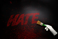 Hand in glove with the brush painting the text hate on a black surface Stock Photo
