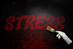 Hand in glove with the brush painting the text stress on a black Stock Image