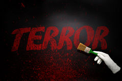 Hand in glove with the brush painting the text terror on a black Stock Photos