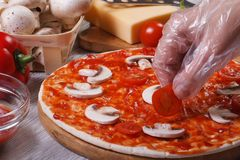 Hand in glove chef puts on a pizza base cherry tomatoes. Stock Photography