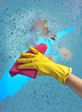 Hand in glove cleaning window on a blue sky background Royalty Free Stock Image