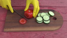 Hand with glove cutting fresh tomato vegetable Royalty Free Stock Images