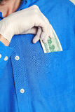 Hand in glove gets bill from his pocket close up Stock Photo