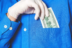 Hand in glove gets bill from his pocket close up Stock Images