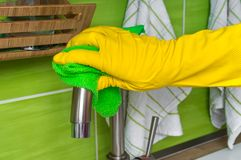 Hand in glove with green rag is wiping faucet in kitchen. Housework and housekeeping concept Stock Photo