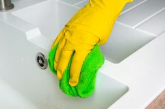 Hand in glove with green rag is wiping sink in kitchen. Housework and housekeeping concept Stock Images