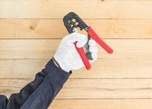 Hand in glove hold wire stripper. Hand in glove holding a wire stripper tool with wall wood background Stock Photo