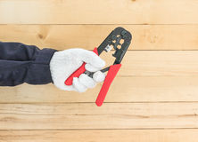 Hand in glove hold wire stripper. Hand in glove holding a wire stripper tool with wall wood background Stock Image