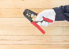 Hand in glove hold wire stripper. Hand in glove holding a wire stripper tool with wall wood background Royalty Free Stock Image