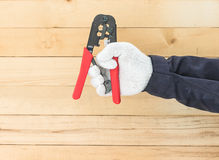 Hand in glove hold wire stripper. Hand in glove holding a wire stripper tool with wall wood background Stock Photography