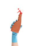 Hand in glove holding brown plastic spray bottle. Stock Image