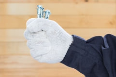 Hand in glove holding metal anchor bolts Stock Photography