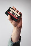 Hand with glove holding an old music tape Royalty Free Stock Photo