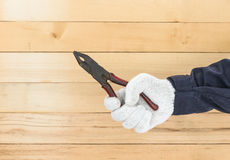 Hand in glove holding pliers Royalty Free Stock Photo