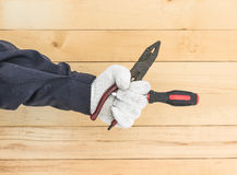 Hand in glove holding screwdriver and pliers Royalty Free Stock Image