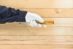 Hand in glove holding screwdriver Stock Photo