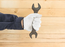 Hand in glove holding spanner Royalty Free Stock Photos