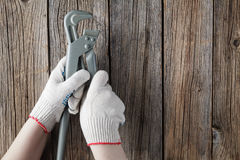 Hand in glove holding wrench on a wooden background Stock Photography