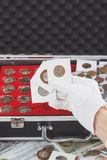 Hand in the glove holds flips with collector coins. Soft focus background Royalty Free Stock Photography