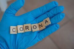 Hand with a glove on holds Scrabble bricks, which form the word: Corona