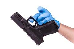 Hand in glove keeps handgun Stock Photo