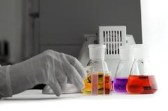 Hand in glove with laboratory flasks royalty free stock photography