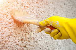 Hand in glove with a paint brush painting on wall. Decorator painting wall with grey paint Stock Photography