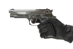 Hand in glove with pistol Royalty Free Stock Images