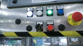 Hand in glove pressing button - starting industrial process. Clip. Worker presses the button at the factory.  Stock Photos