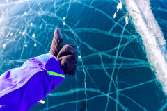 Hand in glove with thumb up against cracked blue ice of Baikal Stock Photos
