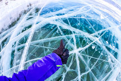 Hand in glove with thumb up against cracked blue ice of Baikal Stock Photo