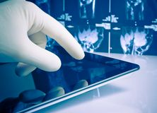 Hand with glove touching modern digital tablet Stock Photo