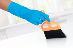 Hand with glove using cleaning broom to clean up. The table Stock Photos