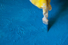 Hand in glove yellow painted blue with bone, close up. Hand in glove yellow painted blue with bone close up Royalty Free Stock Images