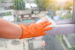 Hand in gloves cleaning window with rag and cleanser spray at ho. Hand  in gloves cleaning window with rag and cleanser spray at home. housework and housekeeping Royalty Free Stock Images