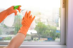 Hand in gloves cleaning window with rag and cleanser spray at ho Stock Photos