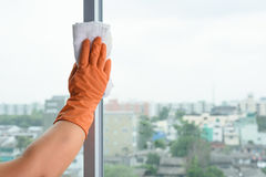 Hand in gloves cleaning window with rag and cleanser spray at ho. Hand  in gloves cleaning window with rag and cleanser spray at home. housework and housekeeping Stock Photo