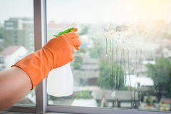 Hand in gloves cleaning window with rag and cleanser spray at ho Stock Image