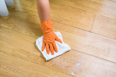 Hand in gloves cleaning Wooden floor with rag and cleanser  at. Hand  in gloves cleaning Wooden floor Stock Photography