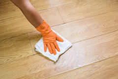 Hand in gloves cleaning Wooden floor with rag and cleanser  at. Hand  in gloves cleaning Wooden floor Royalty Free Stock Photography