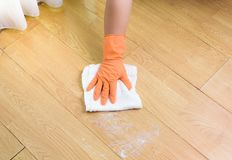 Hand in gloves cleaning Wooden floor with rag and cleanser  at Stock Image