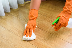 Hand in gloves cleaning Wooden floor with rag and cleanser spra. Hand  in gloves cleaning Wooden floor Royalty Free Stock Photography