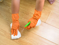 Hand in gloves cleaning Wooden floor with rag and cleanser spra Royalty Free Stock Photos