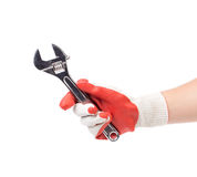 Hand in gloves holding wrench. Stock Photos