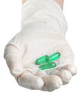 Hand with gloves and pills Stock Images