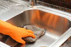 Hand with gloves wiping stainless steel sink with cloth Royalty Free Stock Image