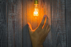 Hand with Glowing bulb on the wood Royalty Free Stock Images