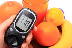 Hand with glucometer, fresh natural fruits, glass of juice Royalty Free Stock Photos